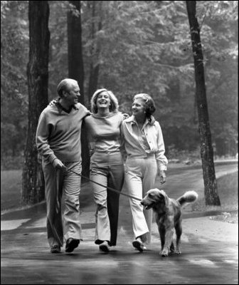 President Gerald R. Ford and Mrs. Betty Ford walk with their daughter, Susan, and family dog, Liberty, at Camp David Aug. 7, 1976.