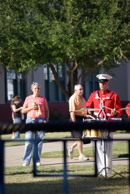 A woman pauses, a man strolls, becoming part of the changing backdrop of the stage for the USMC Drum and Bugle Corps at the Texas State Fair - photo by Ed Darrell