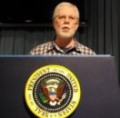 Ed Darrell tries out the Presidential podium and teleprompter