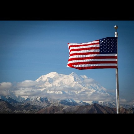 U.S. flag and Denali on an almost-clear day; Department of Interior photo, August 2012 - public domain