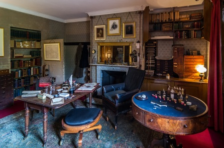 Charles Darwin's Study, Down House. Photo by and copyright held by Bob Radlinski. Radlinski's description: Darwin regularly spent about 5 hours a day here for 40 years and kept a chamber pot behind the partition so that he wouldn't have to trek to the toilet. But he still had time for an active family life with his wife Emma and their 10 children. The low stool with casters was used to spin himself from one desk where he dissected in front of the window to another where he took notes or wrote up labels—the stool the children were allowed to use for their games, punting themselves around the living room with long poles. The sitting room at the back of the house has large windows that go to the floor so that on nice days, the children (and dogs) could roam back and forth from house to garden at will.