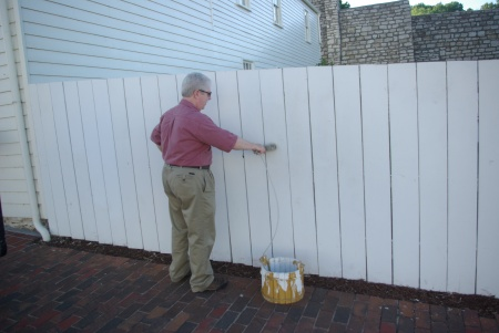 Ed Darrell paints the fence at Mark Twain's childhood home in Hannibal, Missouri