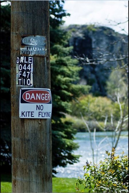 Odd sign, until you realize it's difficult to fly a kite in a canyon and avoid the power lines.  Photo from Poky Tom's Flickr files, Thousand Springs, Idaho.