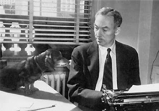 E. B. White at work, with his Dachsund looking on.