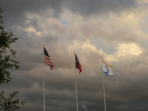 U.S., Texas and University of North Texas at Dallas flags flying on campus, with storm clouds to the South. Photo by Ed Darrell; use encouraged with attribution.