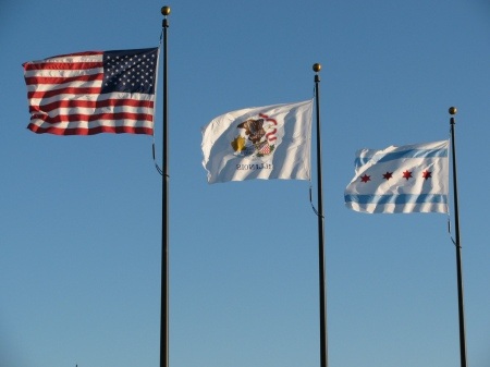 U.S., Illinois and City of Chicago flags in a stiff breeze at the Navy Pier, Chicago. Photo by John Junker, at flickr.