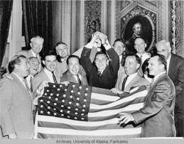 Alaska Territorial Gov. Bob Bartlett in center, with the 49-star flag (Bartlett was one of Alaska's first U.S. senators).