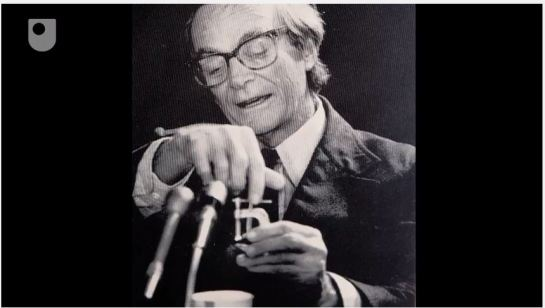 Richard Feynman, working with the Rogers Commission on the Challenger Shuttle Disaster, demonstrating effects of cold on the vital O-rings, with a glass of ice-water, a C-clamp and an O-ring. Open University film screen capture