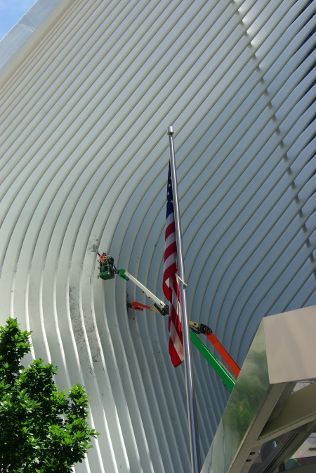 U.S. flag flies in front of construction restoring the sites of the World Trade Center in New York City (bus station opened a few weeks later).