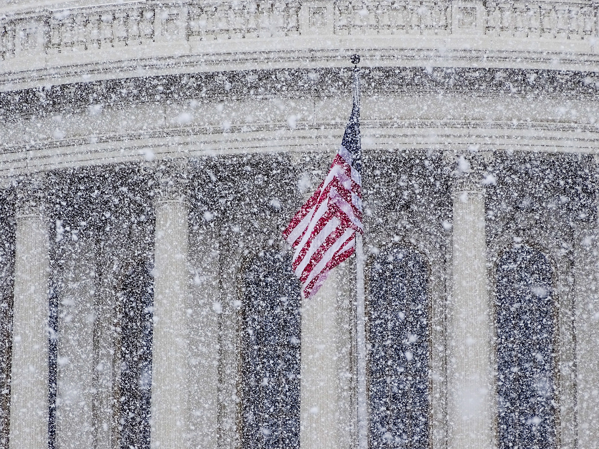 U.S. flag flies at the U.S. Capitol in a snow storm. Photo by Victoria Pickering, Creative Commons license, from Flickr