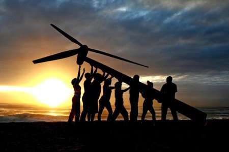 Greenpeace and Tcktcktck volunteers raise a wind turbine on the beach at dawn in Durban, South Africa. Microgrid News image