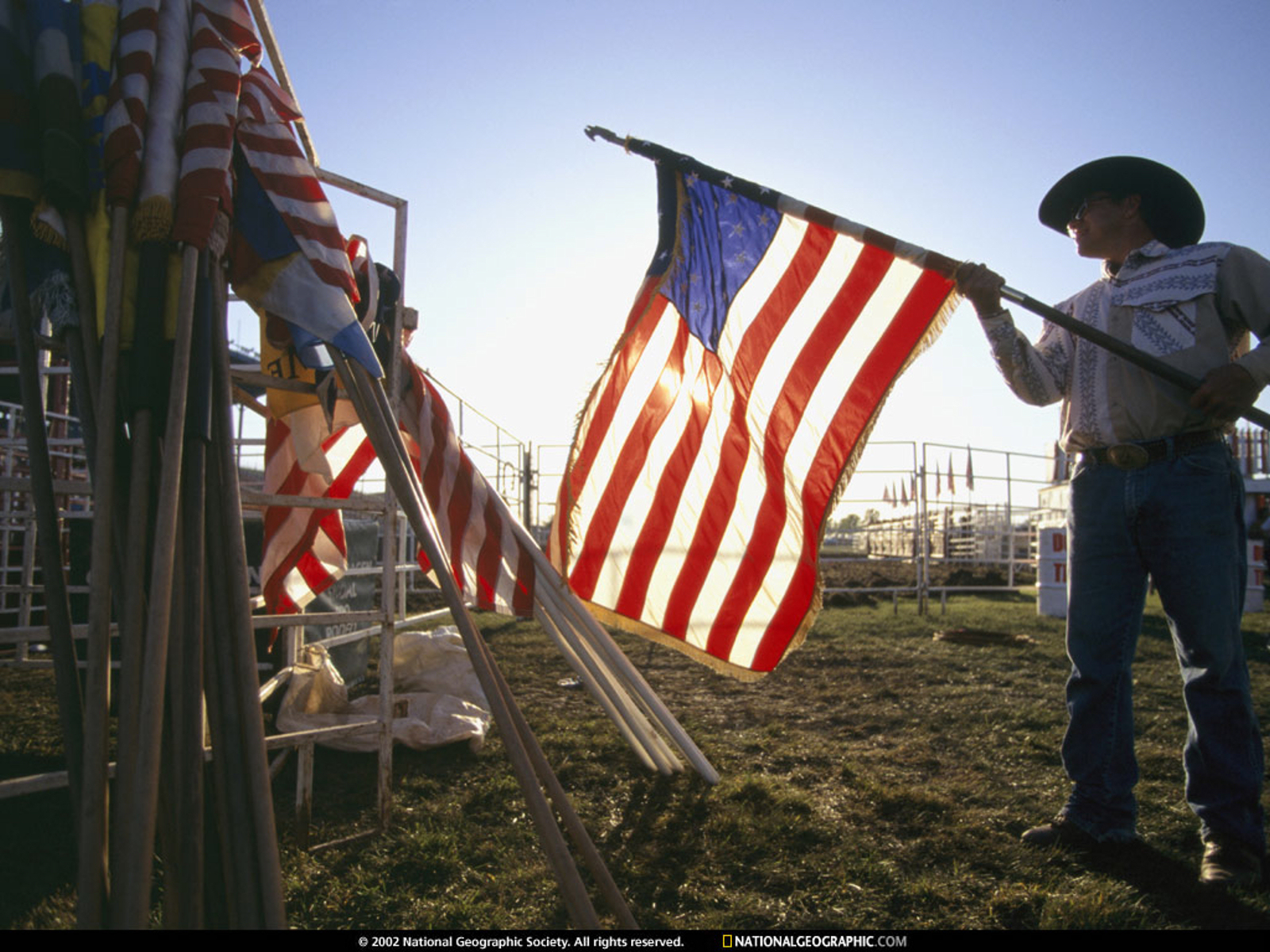 """American Flag, Spencer, Iowa, 1996 – caption from the National Geographic Society: A man rolls up U.S. flags at the end of the Clay County Fair in Spencer, Iowa. """"Although the population of Spencer is only about 12,000, the fair draws some 300,000 visitors. Once a year, rising from the endless flatness of the Iowa countryside, a crowd forms—to stroll, to hear big country music acts like the Statler Brothers, to sell a grand champion boar, to buy a new silo."""" (Photographed on assignment for, but not published in, """"County Fairs,"""" October 1997, National Geographic magazine) Photograph by Randy Olson; copyright National Geographic Society"""