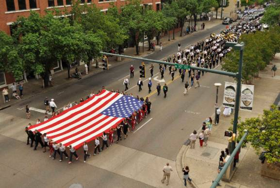 Caption from the Chattannoga Times-Free Press: Students from Soddy-Daisy High School participate in the annual Armed Forces Day Parade by marching while holding a large American flag today on Market Street in downtown Chattanooga. Participants marched the length of Market Street as they were cheered on by crowds gathered on the sidewalk. Photo by Ashlee Culverhouse /Times Free Press.