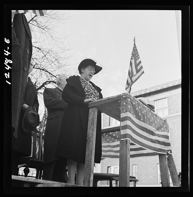 "Illinoisans are big on flag flying. ""Chicago (north), Illinois. Mrs. Alice Burns, who sings on the local radio station, leading the singing of the national anthem at a neighborhood flag dedication ceremony."" Flag dedication ceremony honoring people serving in the military from that block, 1942. Library of Congress image. Jack Delano, photographer, November 1942."