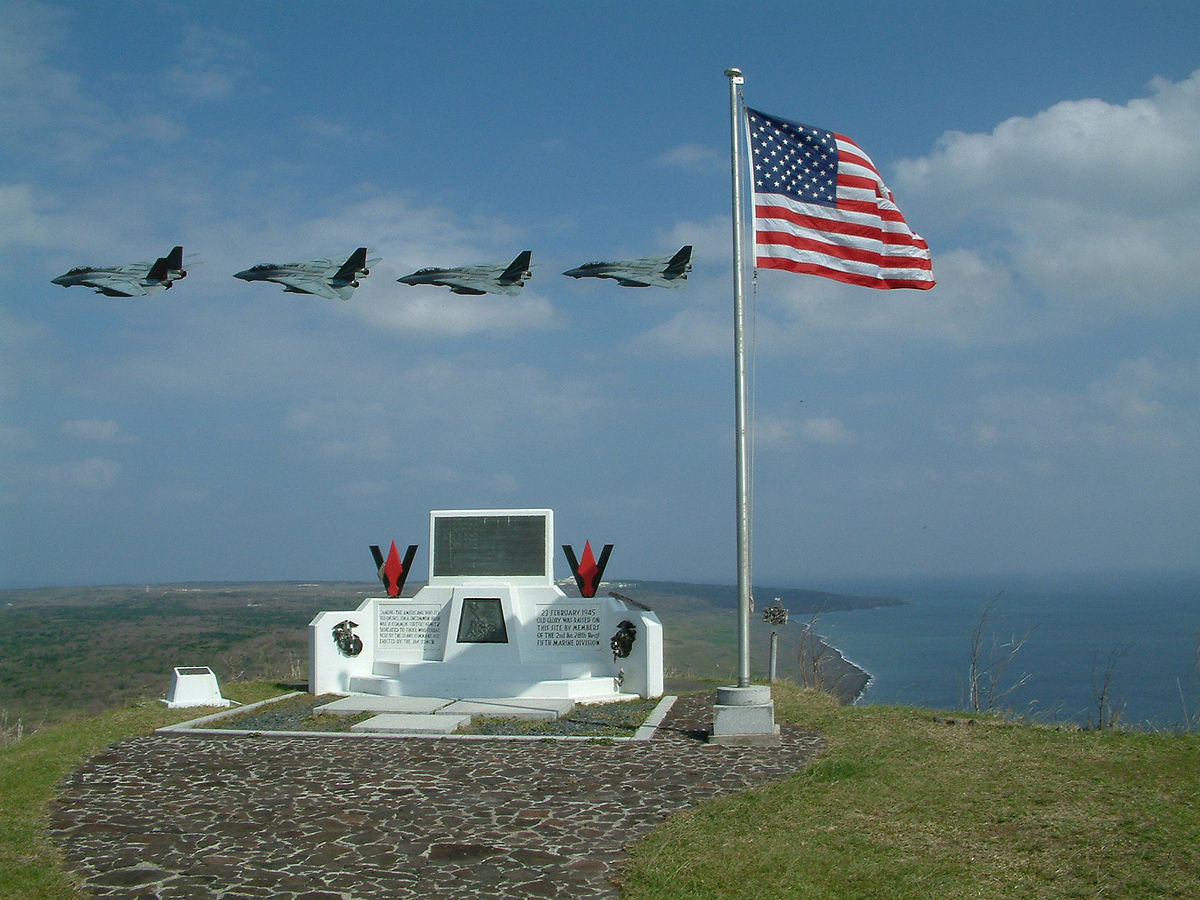 U.S. flag on Mt. Suribachi, Iwo Jima Island - At sea with USS Kitty Hawk (CV-63) Jan. 16, 2003 — F-14 Tomcats assigned to the Black Knights of Fighter Squadron One Five Four (VF-154) fly by Mt. Suribachi on Iwo Jima Island. VF-154 is part of Carrier Air Wing Five (CVW-5) embarked aboard Kitty Hawk, conducting Carrier Readiness Certifications. Kitty Hawk is the Navy's only permanently forward-deployed aircraft carrier and operates out of Yokosuka, Japan. Photo by U.S. Navy, Lt. j.g. Greg Kausner